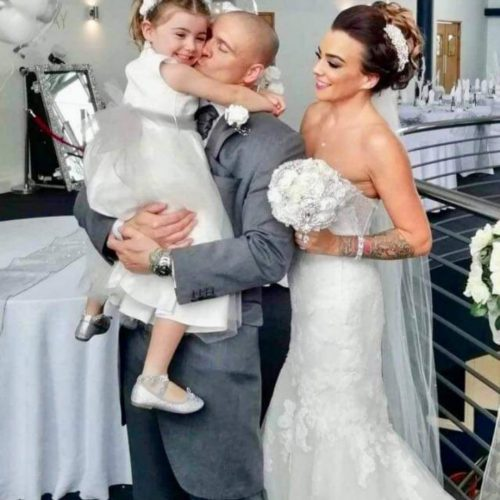 Happy couple and child getting a kiss.